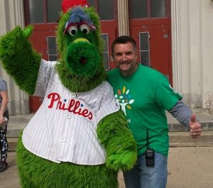 Central President Tim McKenna takes a break on Comcast Cares Day for fun with the Phillie Phanatic.